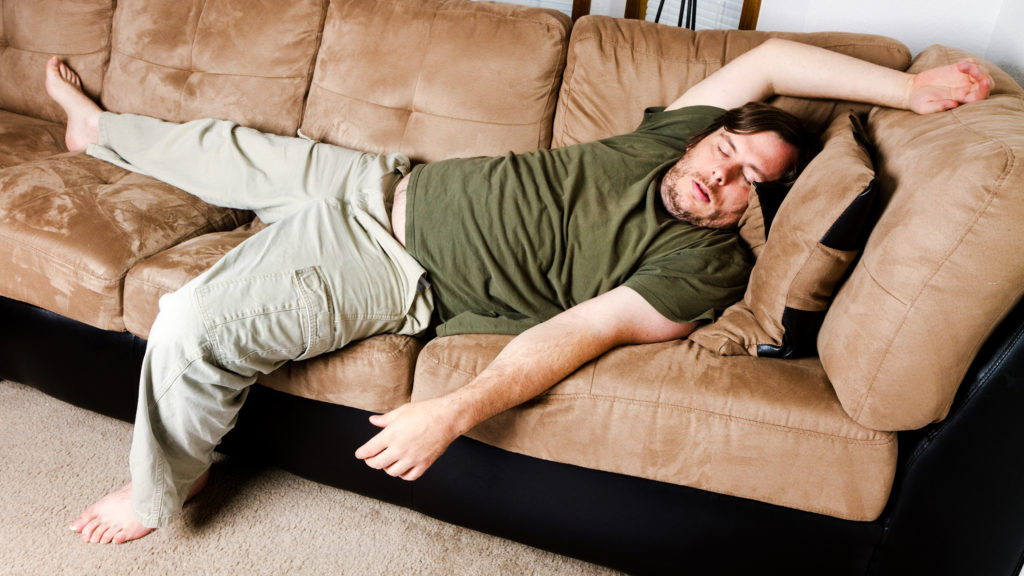 MAn sleeping on the couch just all flung about